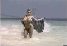Danni Ashe posing in the waves GIF